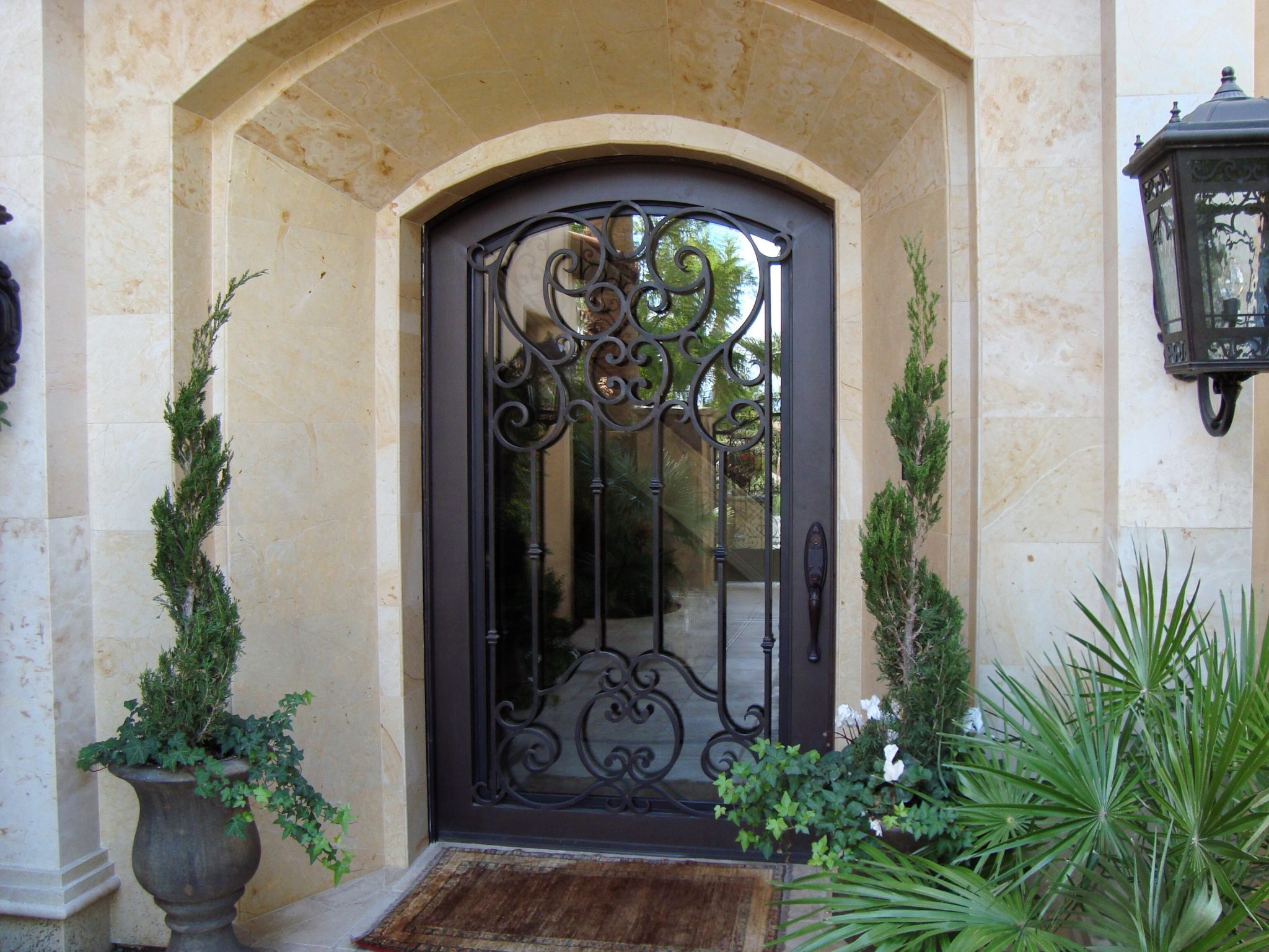 An arched iron entryway door with scroll detail