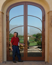A 12 foot tall custom arched double wood entryway door with reflective glass