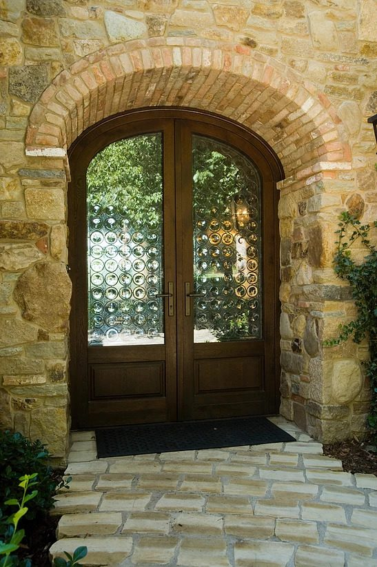 A custom European wood entryway door with decorative glass by Veranda View