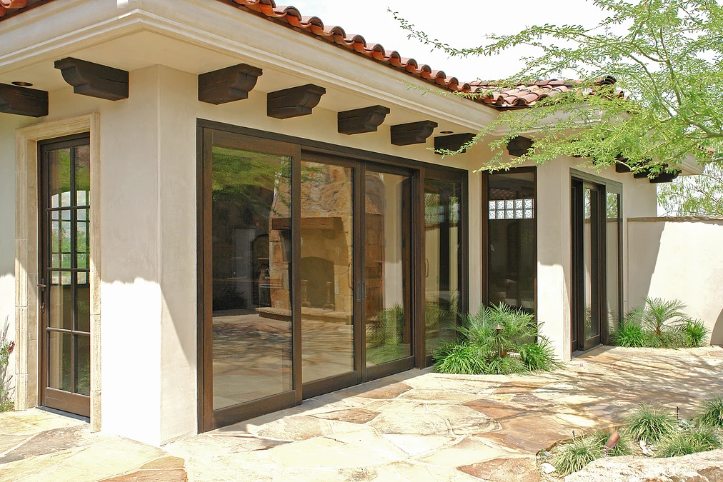 A tuscan style home with custom wood in swing doors, lift slide doors, and fixed windows by Veranda View