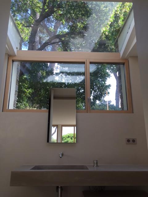 A bathroom with Carminati's Skyline minimal frame wood window