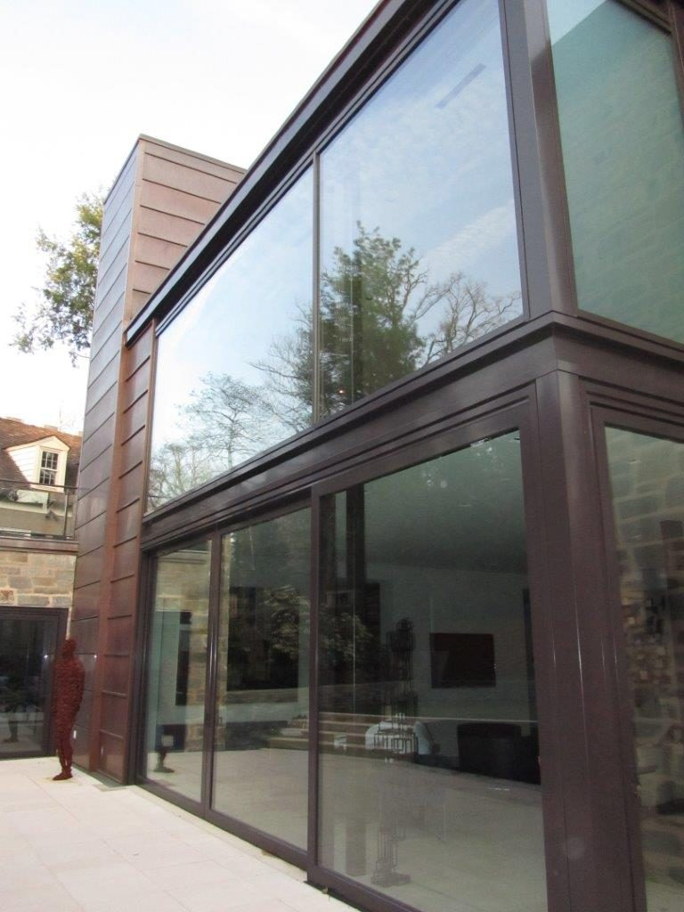 Expansive glass windows and lift slide door in bronze showcase this contemporary home