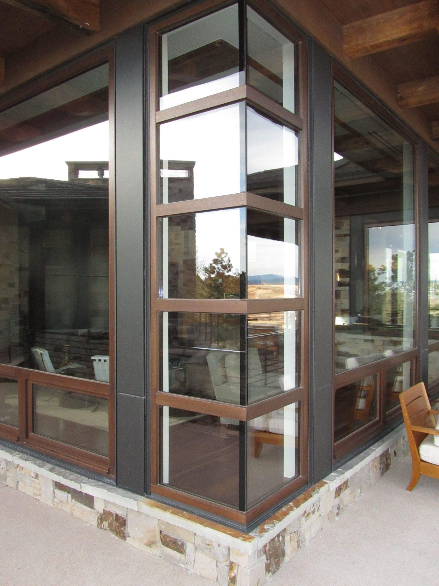 A custom corner meet wood and bronze window by Veranda View