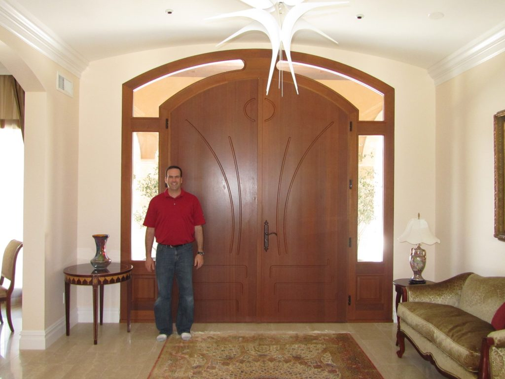 A custom arched double wood entryway door with dual sidelights and a transom by Veranda View