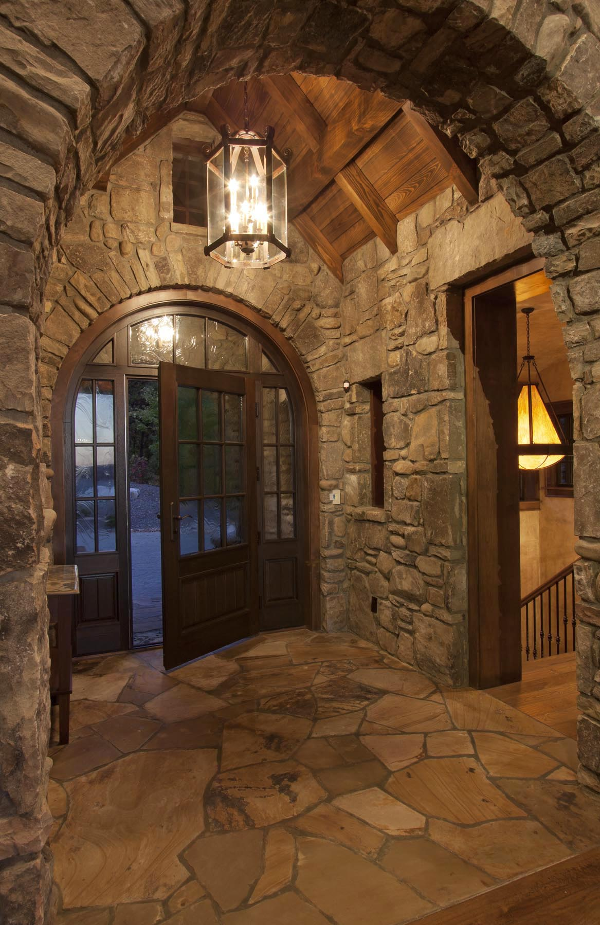 An arched wood and glass entryway door by Veranda View is flanked by side windows and a transom