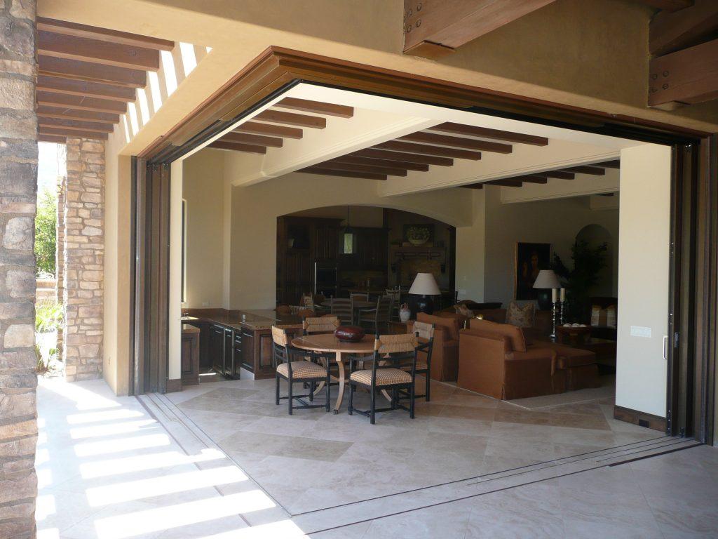 A corner meet wood lift slide pocket door is open to the outdoor living space