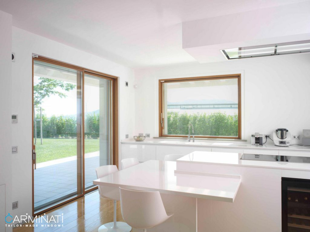 A modern kitchen complete with a minimal frame lift slide door and sliding window by Carminati