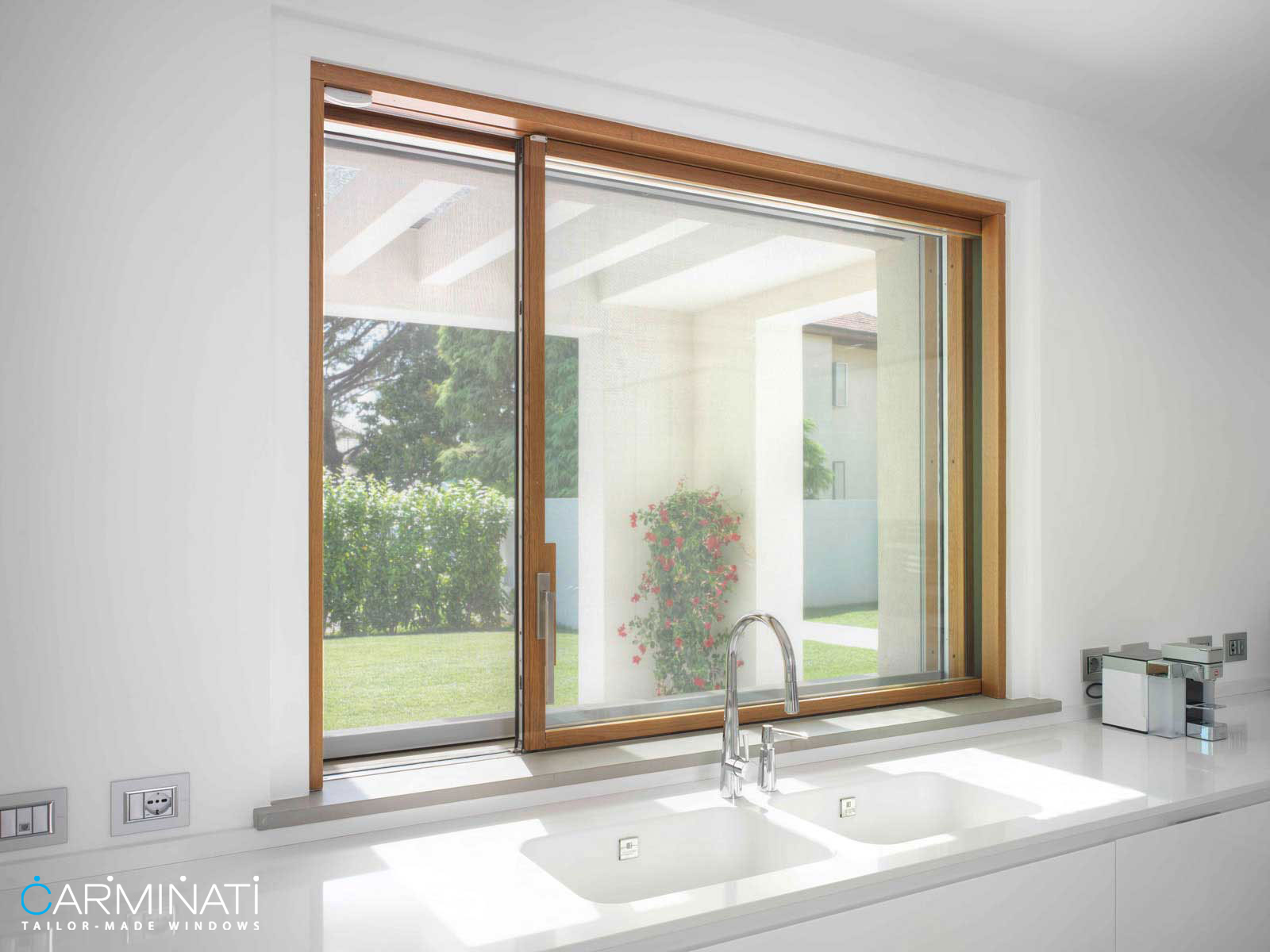 A Skyline minimal frame sliding window in a kitchen from Carminati Serramenti