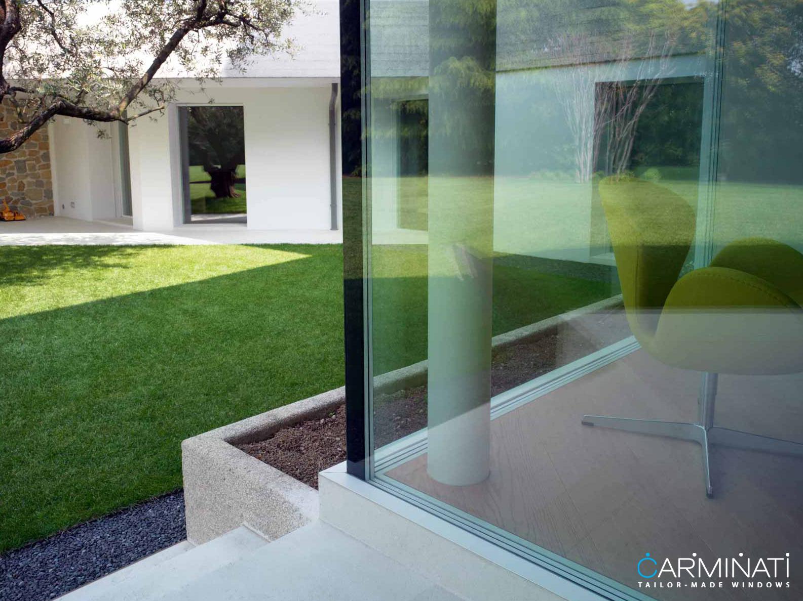 Natural lights fills this contemporary home through an expansive minimal frame glass corner meet window