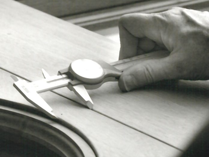 An individual performing measurements during the manufacturing of a wood window