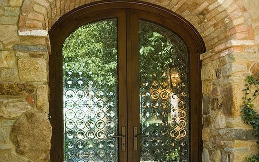 Custom arched wood entryway door with textured glass insets