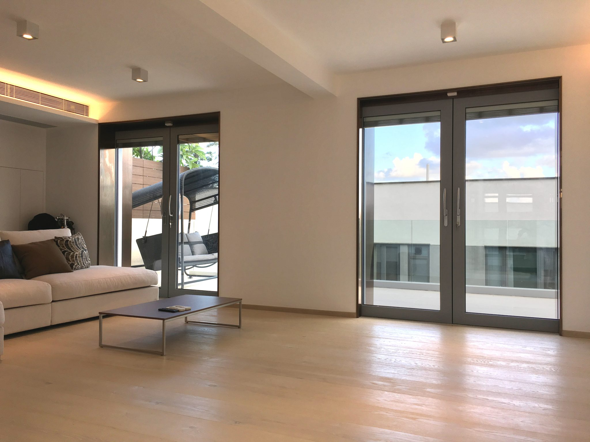 Two sets of aluminum pocket sliding doors open up to an expansive balcony