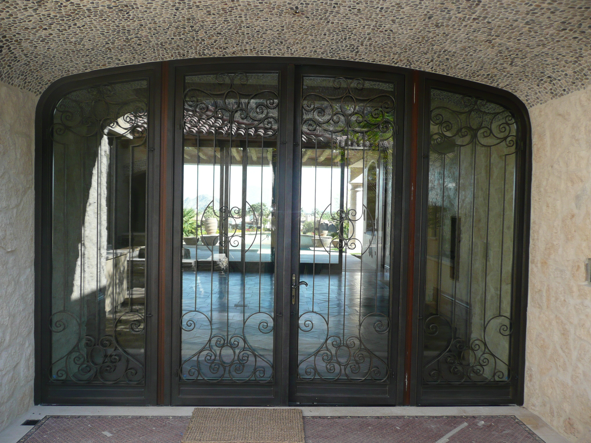 An oversized decorative arched steel entryway door