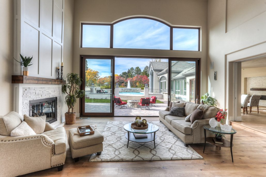 A double lift slide door system with a triple window transom transforms the back wall of the sitting room
