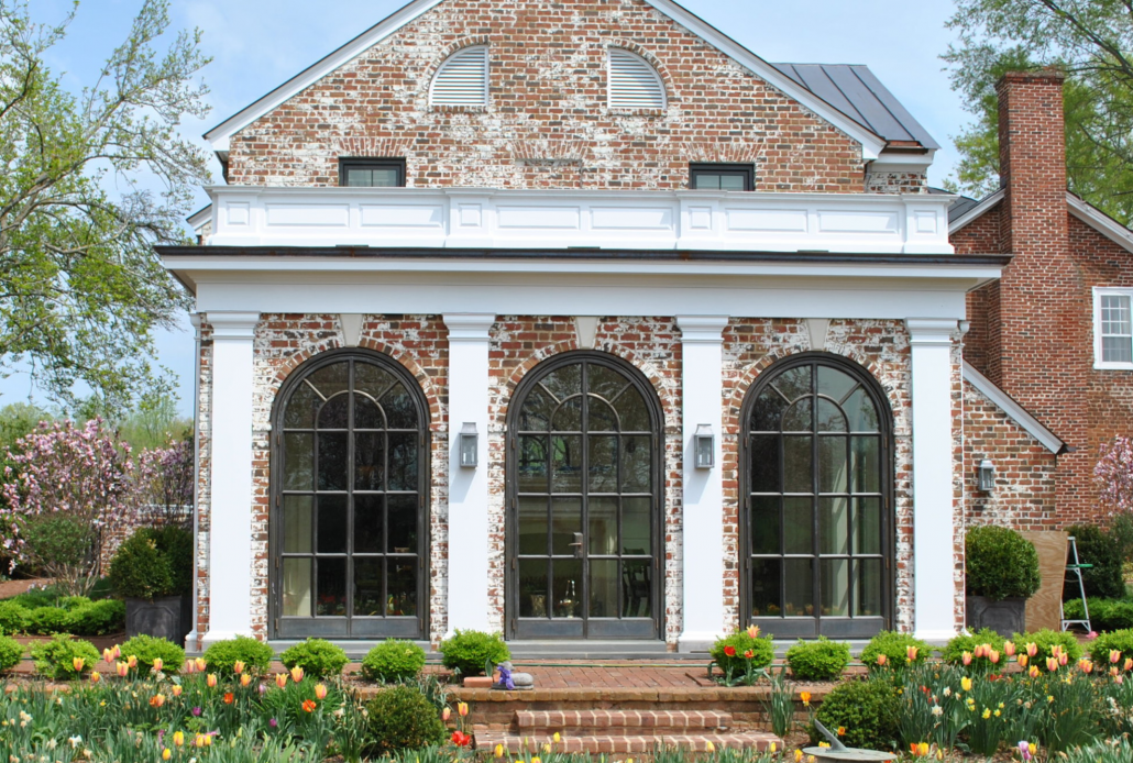 The arched bronze luxury metal windows and doors bring old world charm to this estate