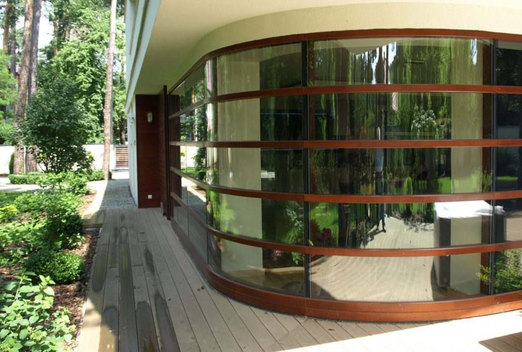 The front of this home features a custom curved wood curtain wall