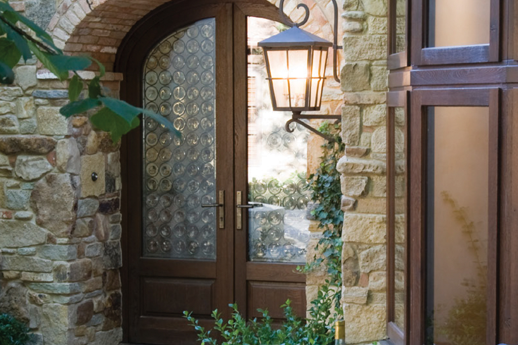 A custom European arched wood double entryway door with textured glass