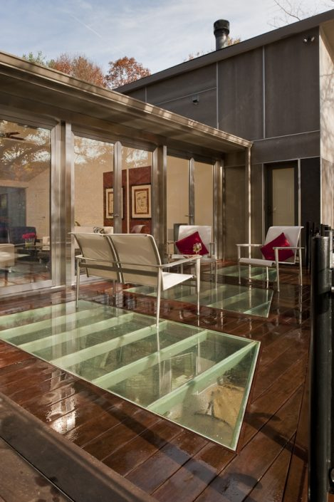 Three sets of stainless steel double pivot doors by Brombal open the living room to the patio