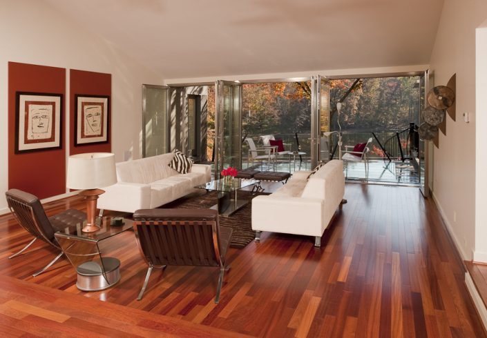 Three sets of stainless steel pivot doors by Brombal open the sitting room to expansive deck outside