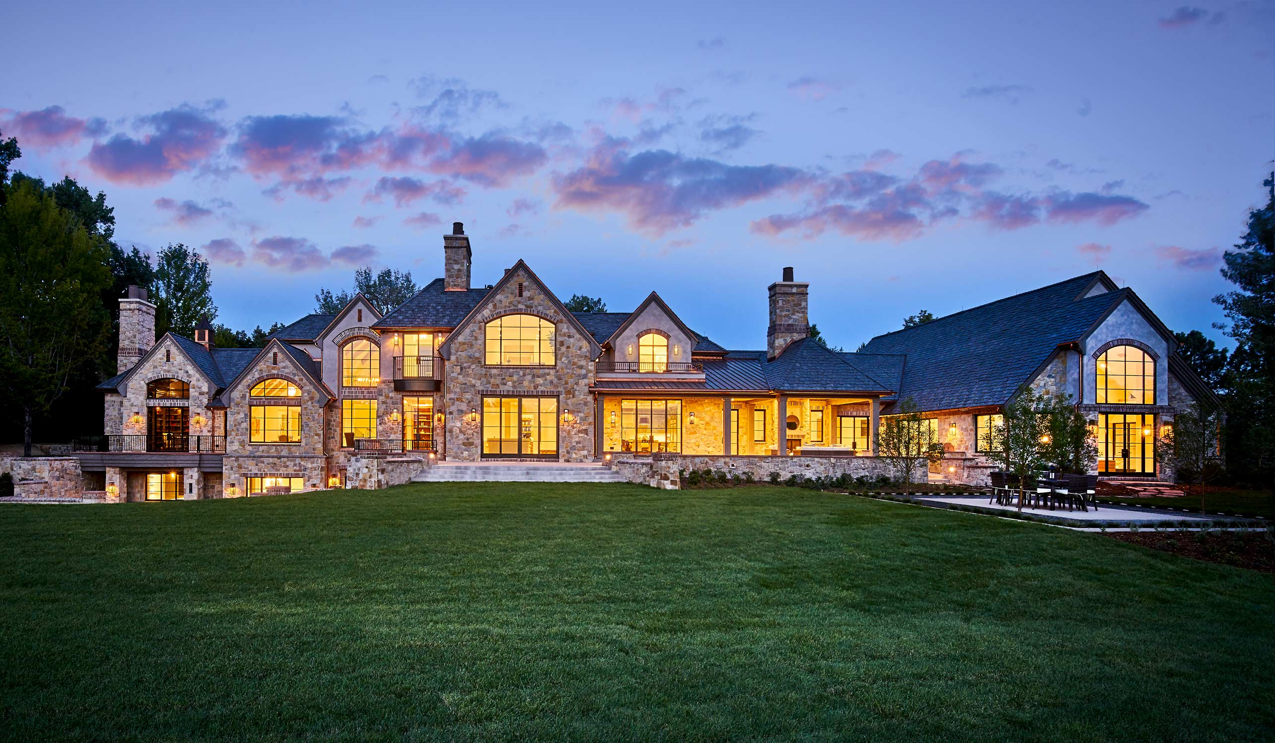 Breathtaking exterior shot at dusk of an estate remodel with Brombal's luxury steel windows and doors