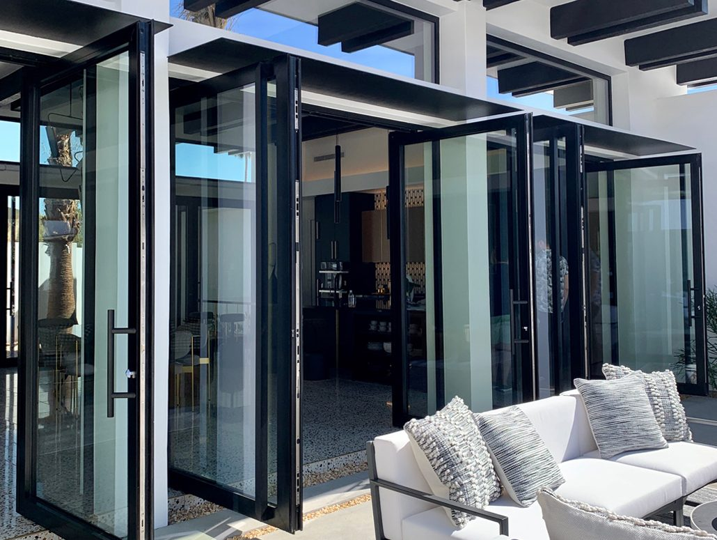 Elegant matte black double-leaf Pivot doors by SPI Finestra open up to the patio in this Palm Springs Villa