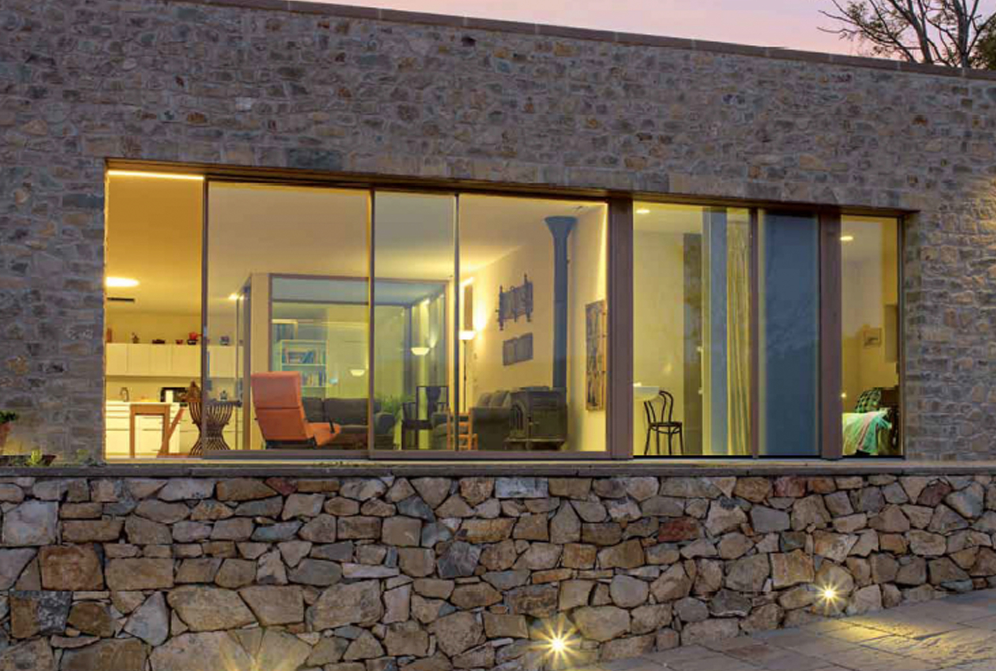 An oversized minimal frame wood sliding window opens the living room to the patio