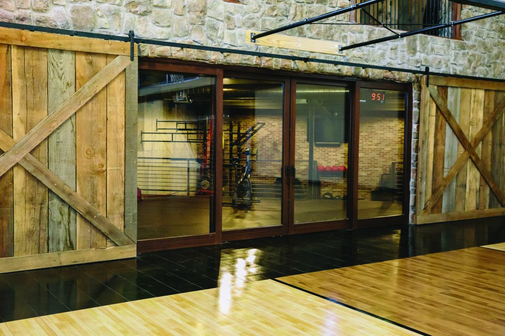 This custom wood lift slide door system separates the basketball court from the workout area