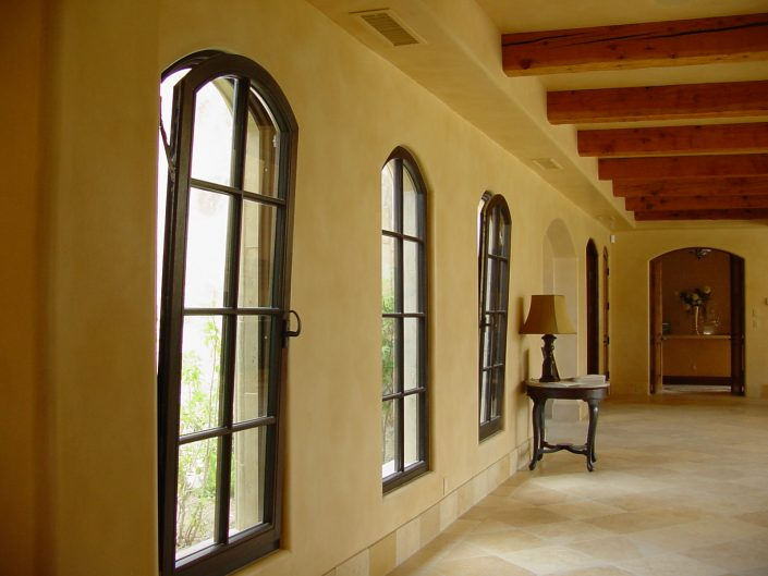 Arched wood tilt turn windows in this estate allows for airflow control