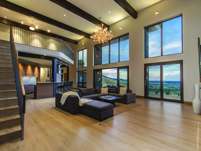 Two story family room with multiple sliding doors and large fixed windows above allows for unlimited views