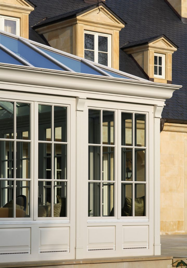 A sunroom featuring traditional white tilt/turn windows