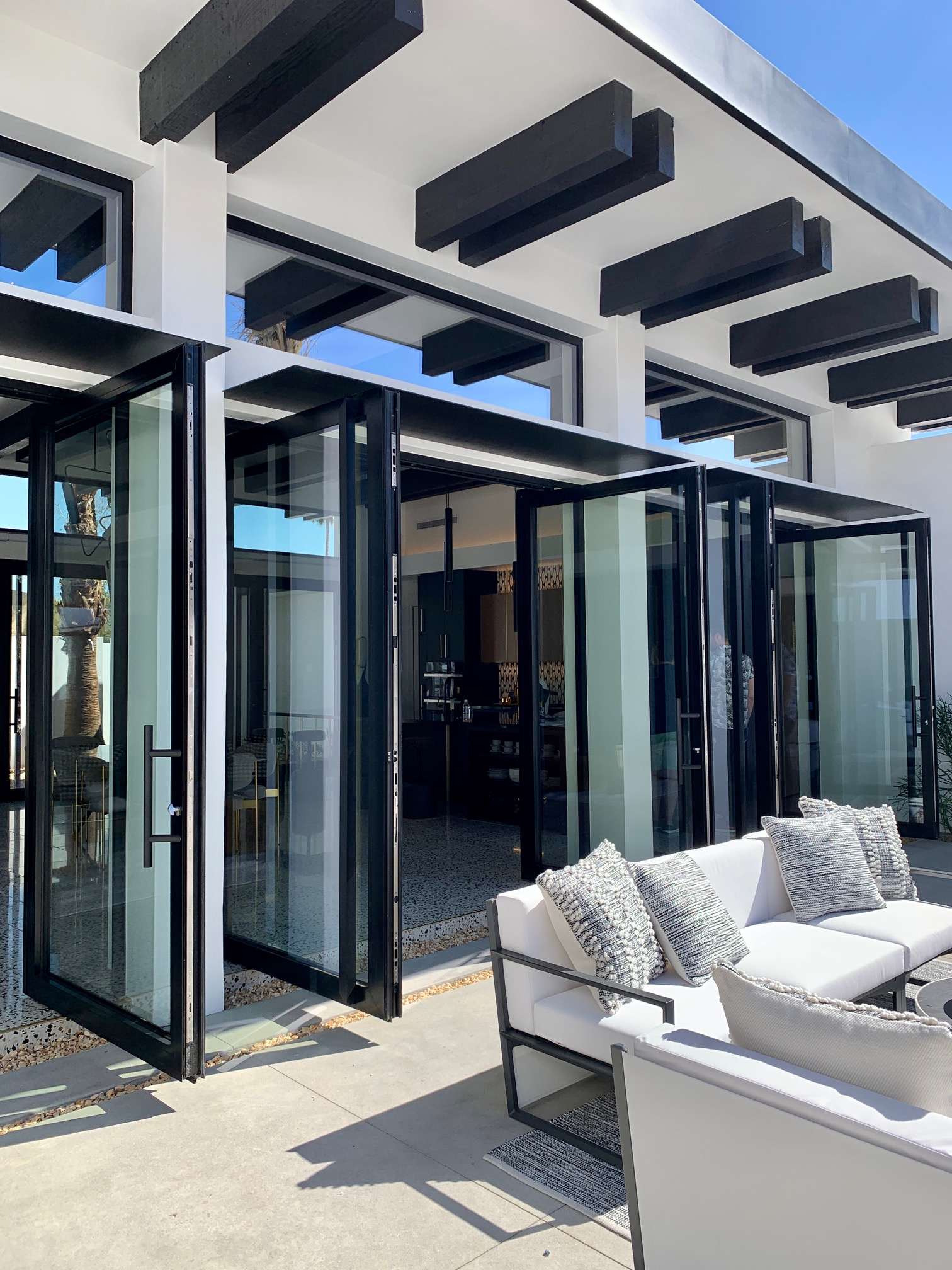 Elegant matte black double-leaf aluminum pivot doors by SPI Finestra open up to the patio in this Palm Springs Villa