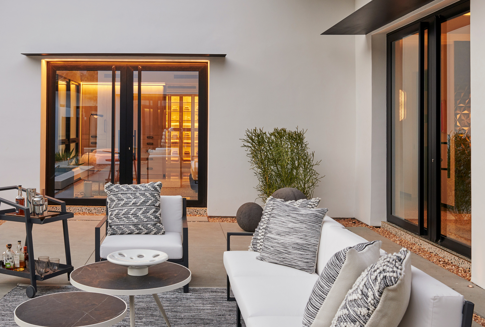 Minimal frame double leaf aluminum pivot doors finished in a matte black are featured in this California villa
