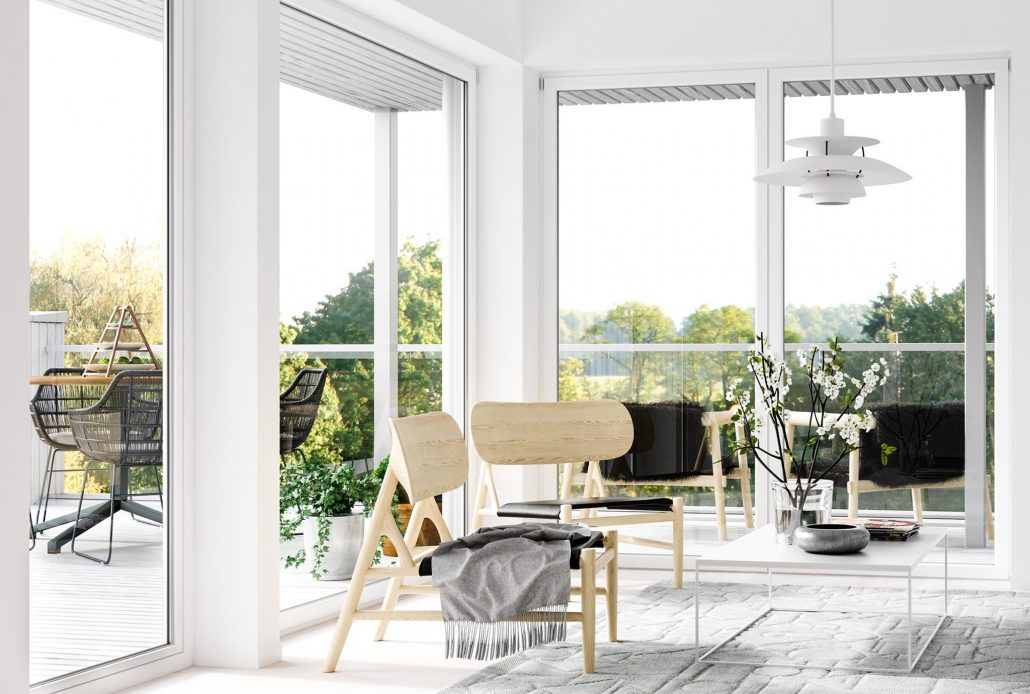 A sitting area is blanketed in natural light from minimal frame aluminum windows and doors