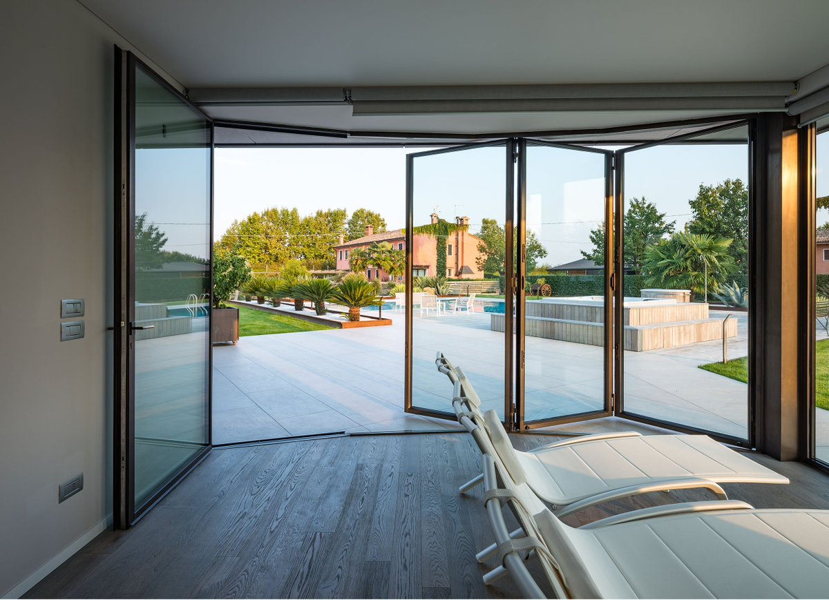 A thermally broken minimal frame folding steel doors open this pool house to the expansive outdoor pool
