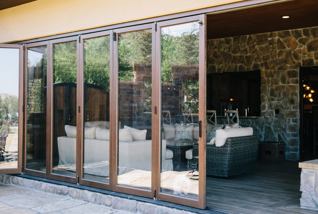 An eleven panel wood folding door system opens the downstairs living area to the pool and patio
