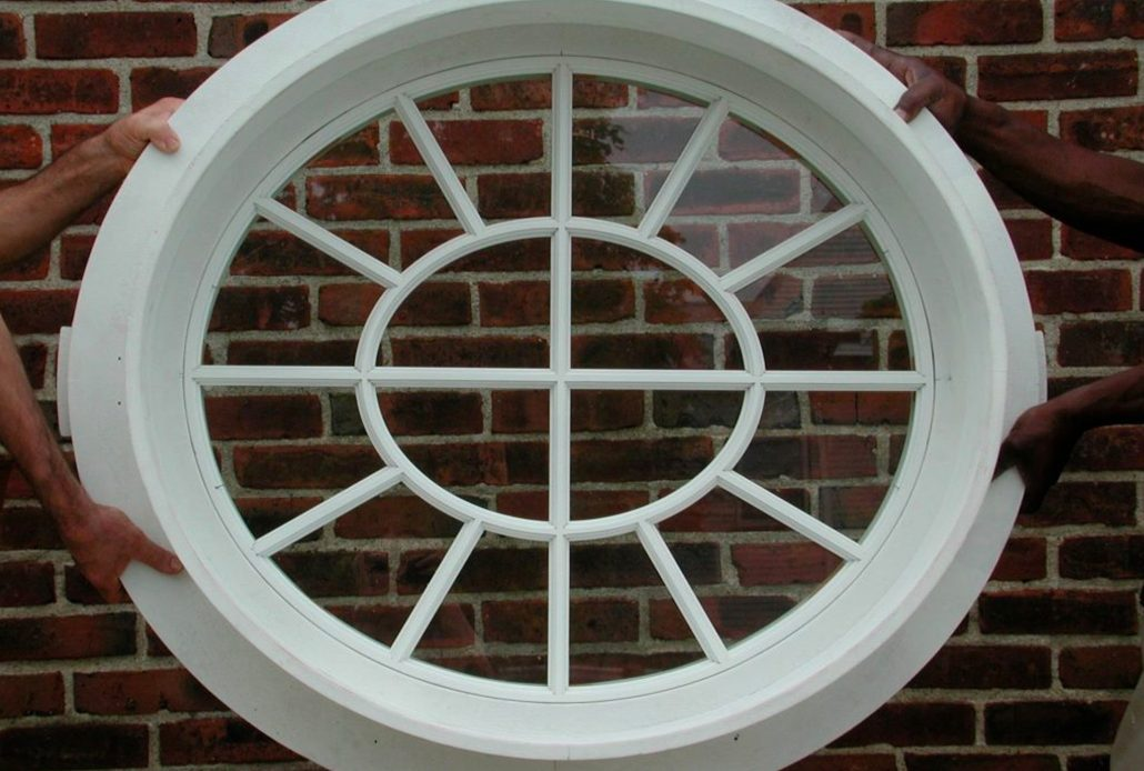 Installers carry a circular wood window historical replica into the house for placement