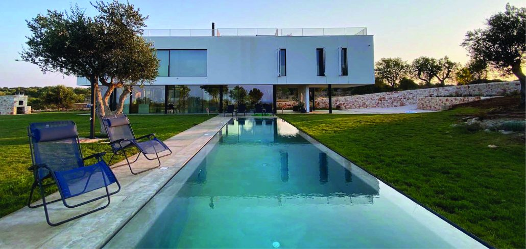 Black minimal frame aluminum windows and doors create expansive views in this contemporary seaside villa