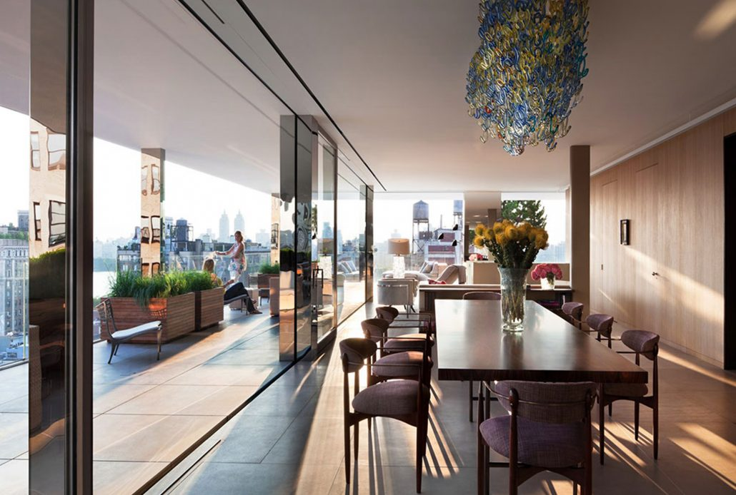 Minimal frame stainless steel windows and doors with expansive glass creates glass walls with views of the city