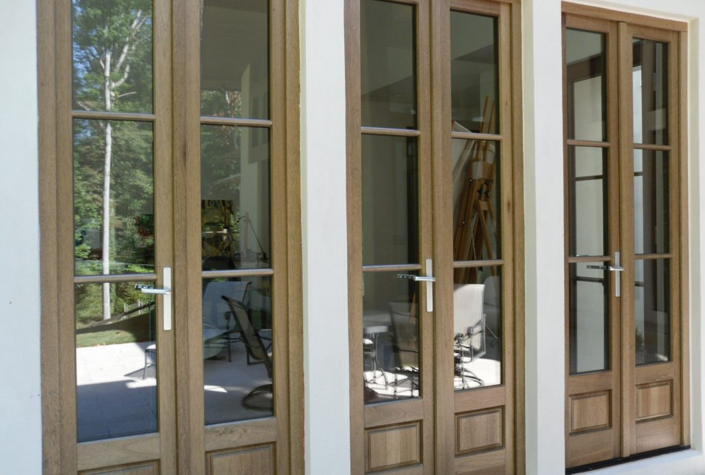 Three sets of custom wood inswing doors open the inside living space to the outdoor lounge