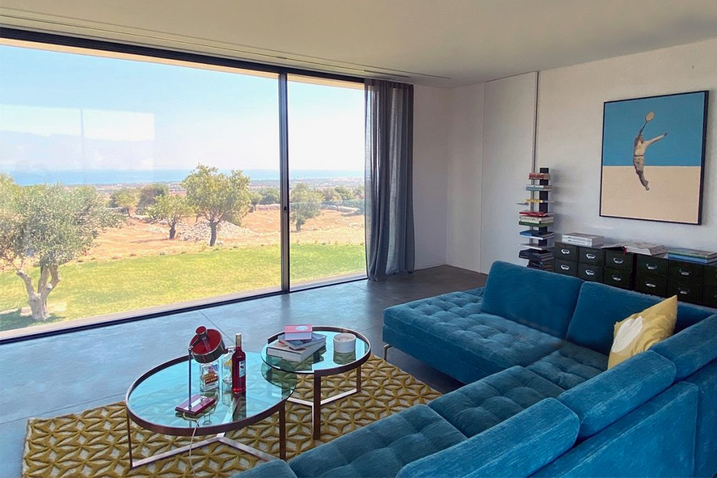 An expansive minimal frame window and door from Contempo Vista gives the homeowner views of the ocean while relaxing
