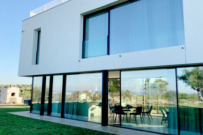 A minimal frame lift slide door system by Contempo Vista expands the living space to the outdoor lounge area