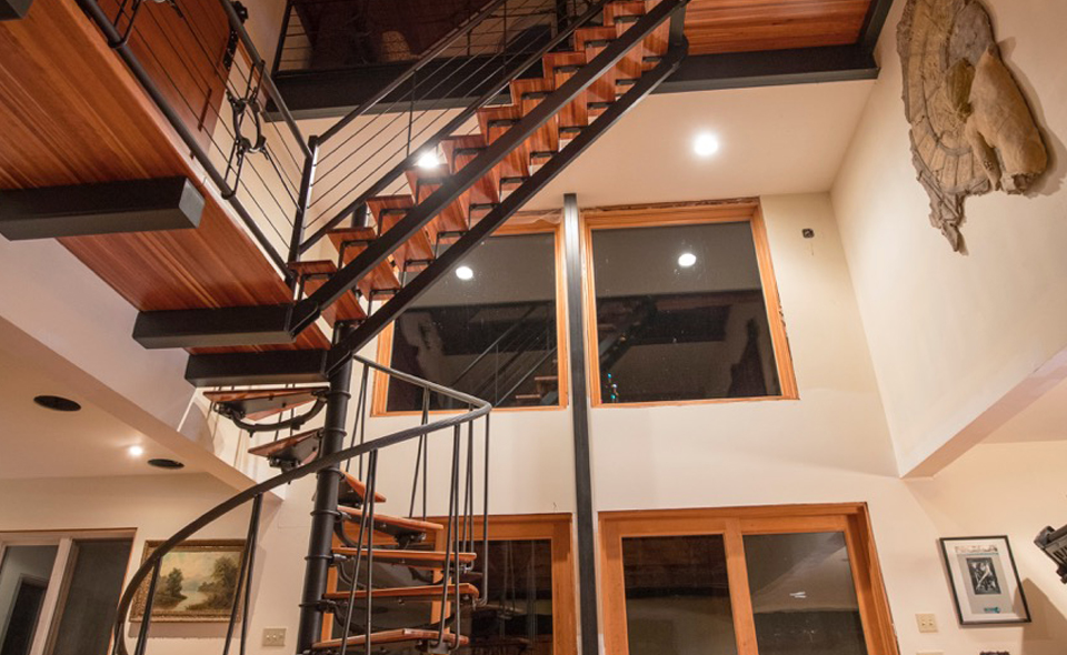 Vintage Steel manufactured a hot rolled steel spiral staircase for the first level and a regular staircase for the second level.