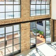 Hot rolled steel door and window systems flood this loft with natural light