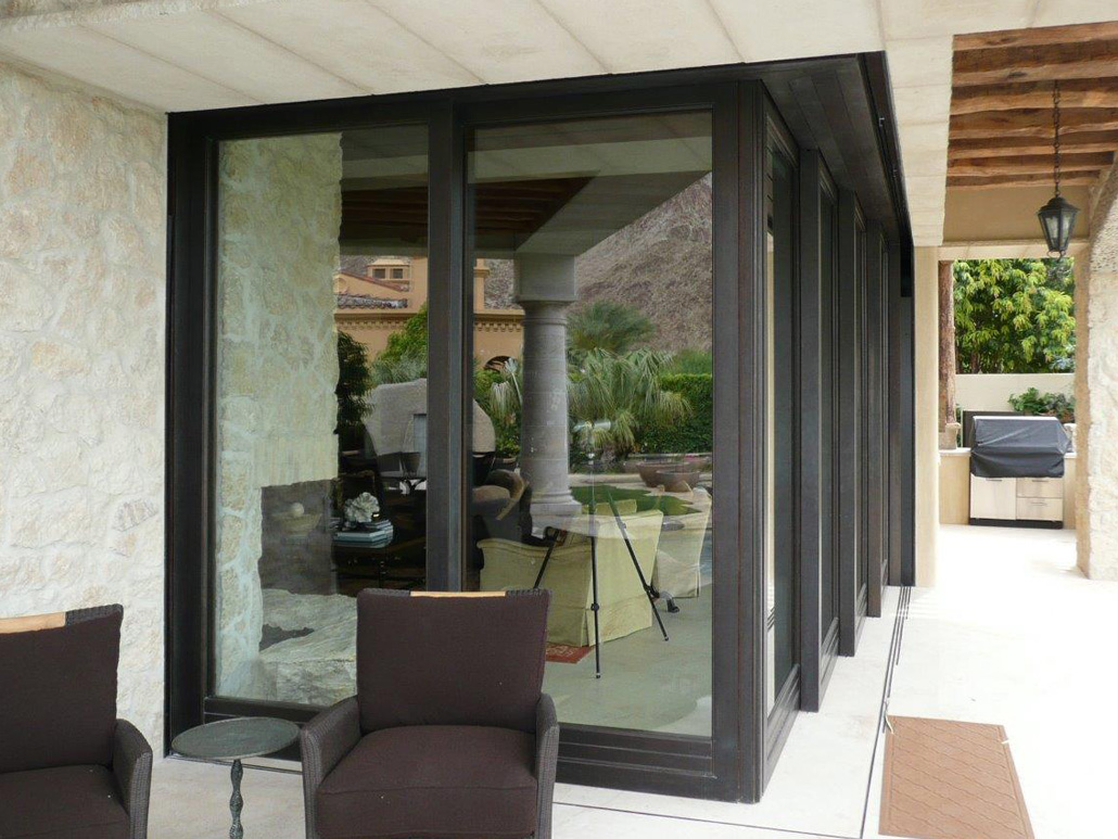 A multi-panel bronze corner meet lift slide door expands the living space to the outdoor sitting area