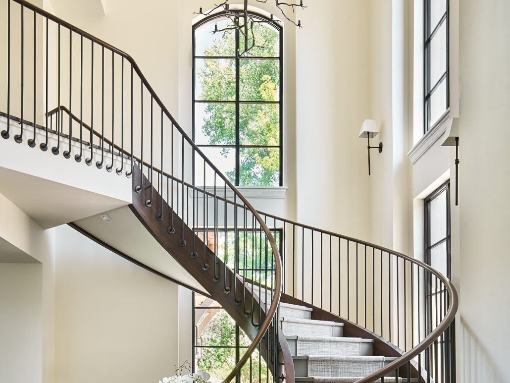 Thermally broken steel windows and doors surround the winding staircase infusing natural light into the home