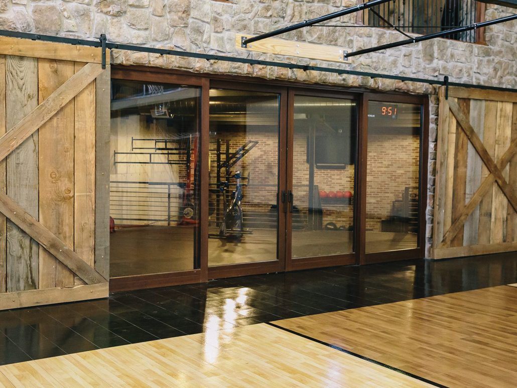 A wood lift slide door separates the gym from the workout room