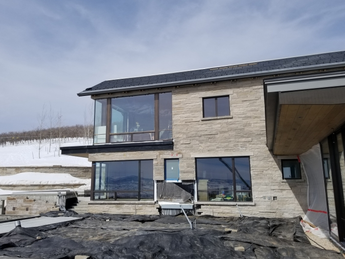 The installation of oversized steel windows is complete in this section of the expansive mountain retreat.