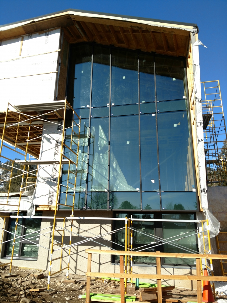 Scaffolding is used to aid in the installation of the oversized glass for these steel windows.