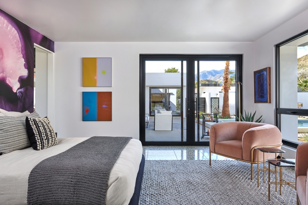 a pair of oversized aluminum pivot doors finished in black open the bedroom out to the pool area