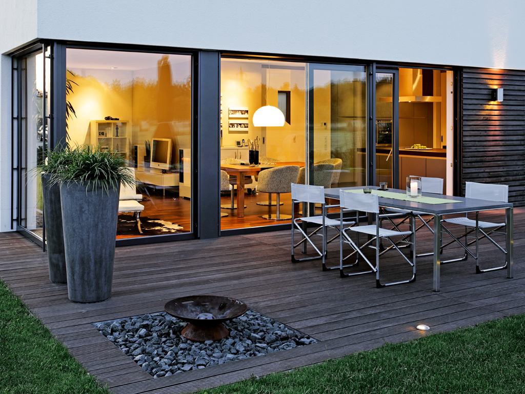 A PVC sliding door from SPI Finestre expands the living space to the outdoor lounge.